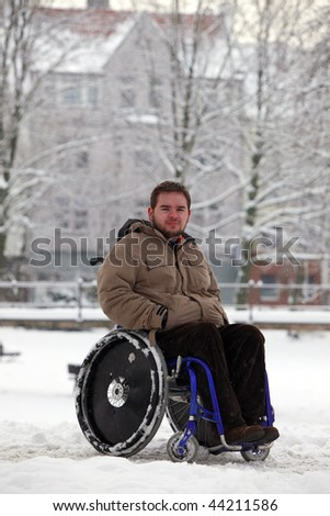 disabled young man in wheelchair at the park - stock photo
