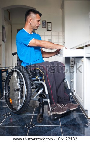 Disabled young man in wheelchair takes cutlery out of the box - stock photo