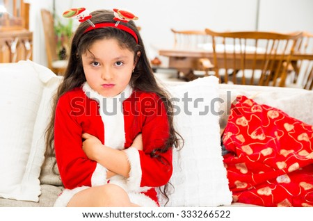 Disappointed and grumpy little girl wearing christmas dress and crossing arms - stock photo