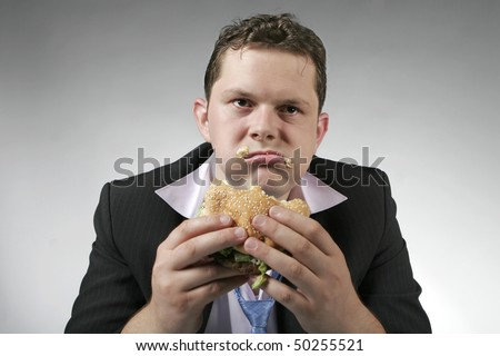 Disappointed businessman eating fast food burger - stock photo