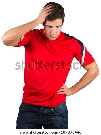 Disappointed football fan in red on white background - stock photo