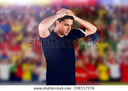 Disappointed football player looking down against blurry football pitch with crowd - stock photo