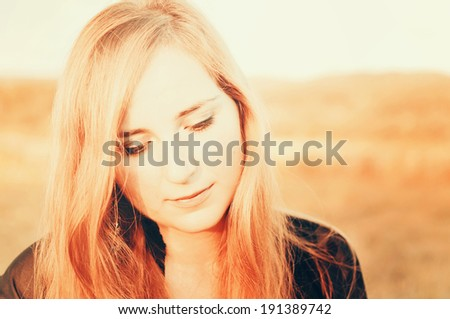 Disappointed girl looking towards the ground. Vintage effect applied. - stock photo