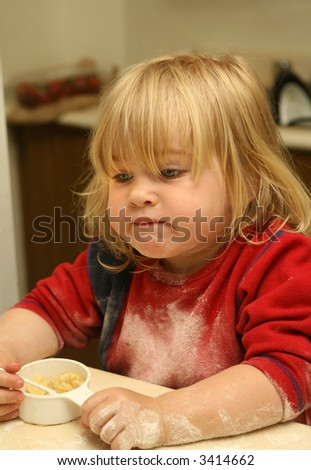 disappointed little girl contemplating the perfect pie that didn't turn out the way she wanted - stock photo