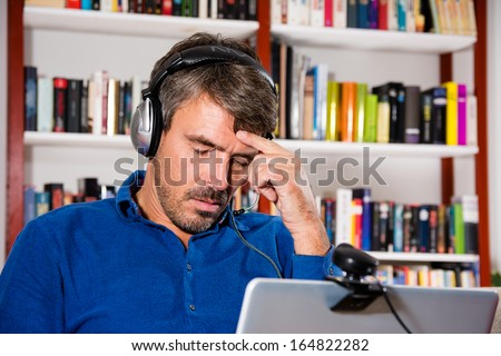 Disappointed man at video chat - stock photo