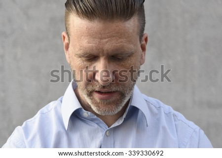 disappointed man in blue shirt with head hanged down - stock photo
