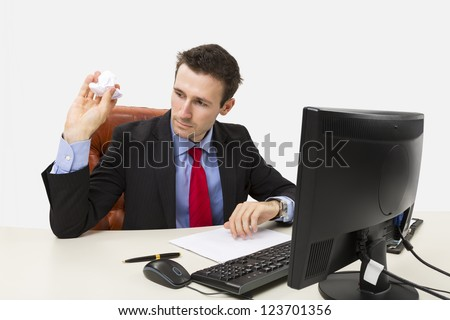 Disappointed manager throwing a crumpled paper in front of his computer at office. - stock photo