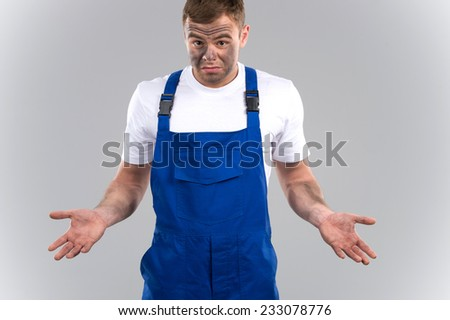 Disappointed mechanic in overall against grey background. dirty worker showing negative emotions - stock photo