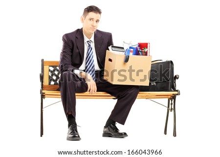 Disappointed redundant businessperson in black suit sitting on a bench with a box of belongings isolated on white background - stock photo