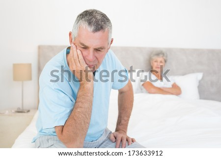 Disappointed senior man with woman in background at home