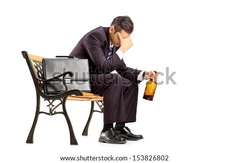 Disappointed young businessperson sitting on a wooden bench and holding a bottle isolated on white background - stock photo
