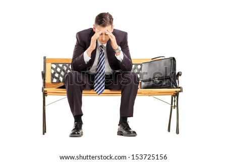 Disappointed young businessperson sitting on a wooden bench isolated against white background - stock photo