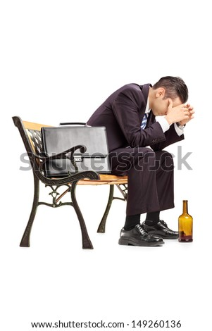Disappointed young businessperson sitting on a wooden bench isolated on white background - stock photo