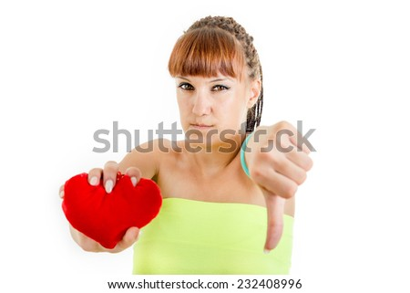 Disappointed young woman sadly holding heart showing thumb down and hates being hurt suffering from love - stock photo