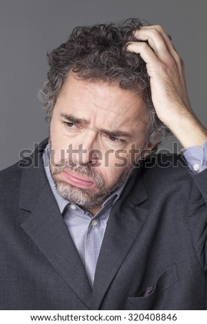 disappointment concept - grumpy middle age businessman with salt and pepper hair scratching his head expressing management discouragement and corporate resignation