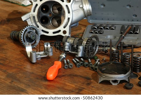 Disassembled four-stroke Motorcycle engine of motocross bike scattered on old wooden workbench.  Socket set and nut driver included. - stock photo