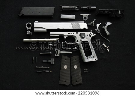 Disassembled handgun on black background,  - stock photo