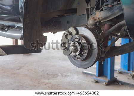 Disc brake on car, in process of new tire replacement,Car brake repairing in garage, automotive service station,mechanic changing a wheel and Tires
