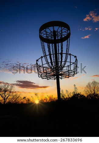 Disc golf basket in the park at sunset or sunrise - stock photo
