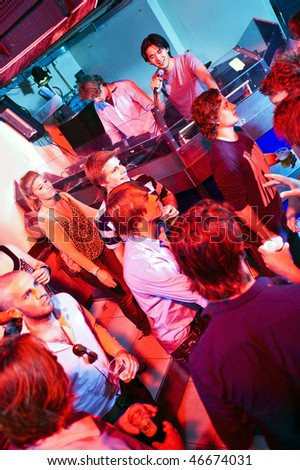 Disc Jockey and Microphone Controller in a crowded club - stock photo