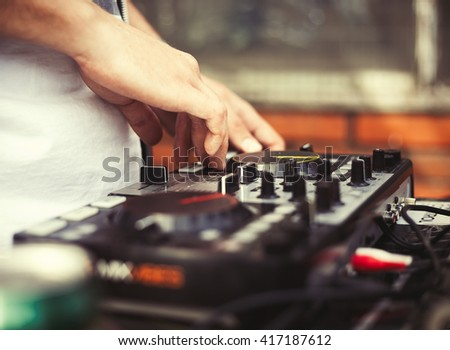 Disc jockey playing music on modern midi controller turntable. New digital DJ technology for mixing audio tracks from notebook or flash drive. Warm film hipster colors - stock photo