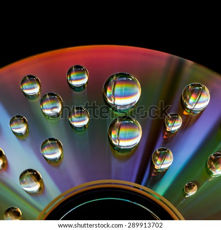Disc with water drops and colorful reflection - stock photo