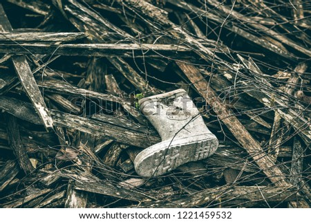 Discarded dirty rubber gumboot isolated on an outdoor background image in landscape format with copy space