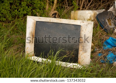 Discarded old TV set on a field - stock photo