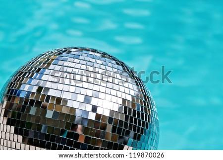 Disco ball beside blue swimming pool water - stock photo