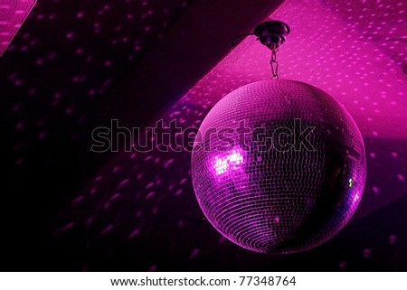 Disco ball in motion reflecting pink light in night club with copy-space - stock photo