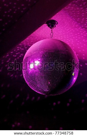 Disco ball in motion reflecting pink light in night music club with copy-space