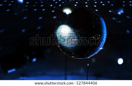 Disco ball with blue rays over dark night club interior background