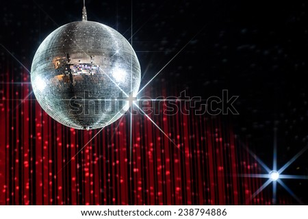 Disco ball with stars in nightclub with striped red and black walls lit by spotlight - stock photo
