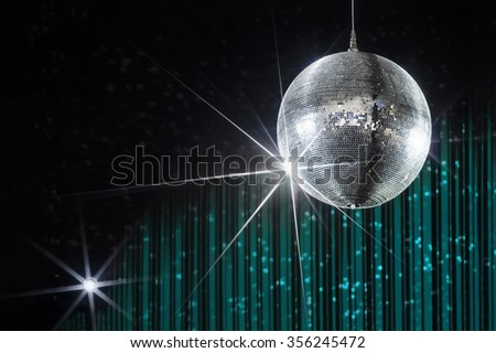 Disco ball with stars in nightclub with striped turquoise and black walls lit by spotlight, party and nightlife entertainment industry  - stock photo