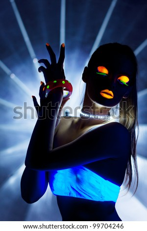 Disco girl with glow make-up dance in uv light - stock photo