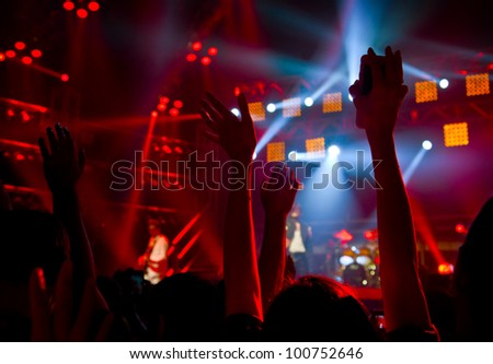 Disco party concert with large group of happy dancing people, silhouette of hands up in the air over blur red colorful stage lights, active lifestyle entertainment, music nightclub, night life concept - stock photo