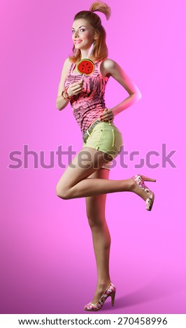 Disco redhead girl with fun hairstyle and big lollipop smiling and dancing on pink background