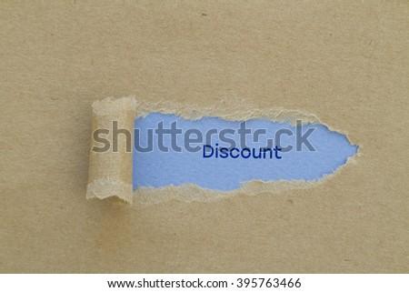 Discount word written under torn paper. - stock photo