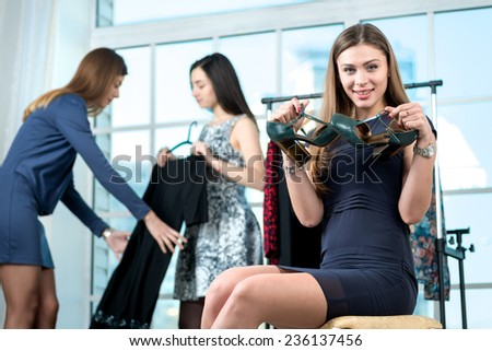 Discounts on shoes. Smiling girl does chooses shoes in their hands and looking into the camera while her friends choose dress on a hanger. Girls having fun together doing shopping - stock photo