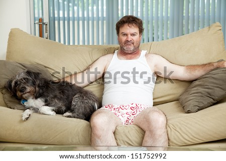 Discouraged unemployed man at home in his underwear, sitting on the couch with his dog.   - stock photo