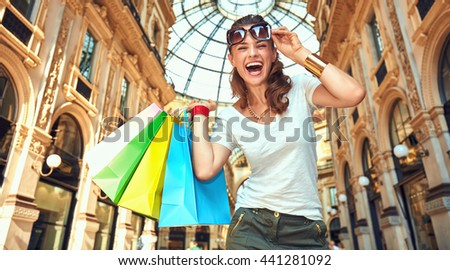 Discover most unexpected trends in Milan. Portrait of smiling fashion woman with eyeglasses and colorful shopping bags in Galleria Vittorio Emanuele II - stock photo
