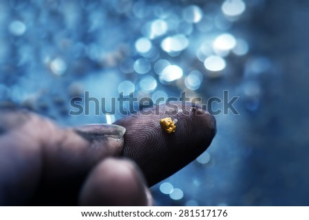 Discovery of gold. Gold on finger tips with shallow stream in background.Gold prospecting. Very shallow depth of field due to subject size. - stock photo