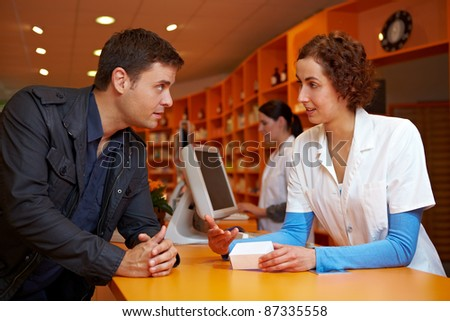 Discrete talk between customer and pharmacist in pharmacy - stock photo