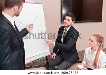 Discussing business strategy. Group of business people in formal wear sitting together at the table while handsome man standing near whiteboard and pointing it with smile - stock photo