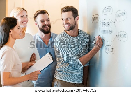 Discussing business together. Group of cheerful young business people in smart casual wear discussing something while standing together near whiteboard  - stock photo