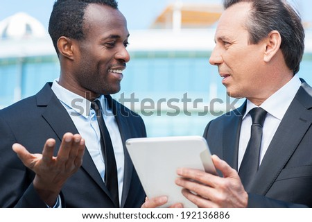 Discussing business. Two cheerful business men talking outdoors while one of them holding digital tablet  - stock photo