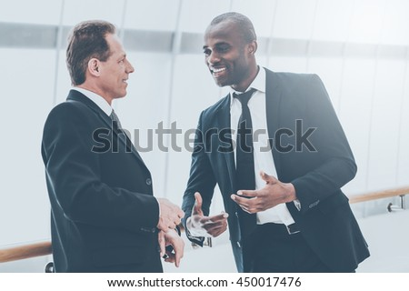 Discussing business. Two cheerful business men talking to each other and gesturing - stock photo