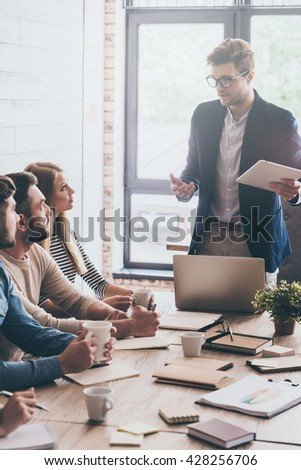 Discussing business. Young handsome man in glasses gesturing and discussing something with his coworkers at business meeting - stock photo