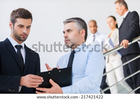 Discussing contract. Two confident businessmen discussing something and looking at clipboard while standing at the staircase together with people in the background  - stock photo