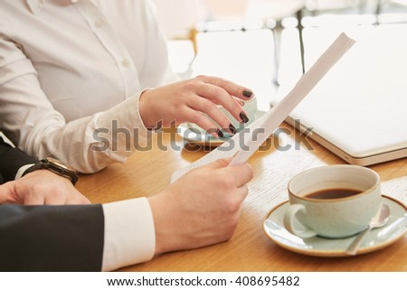 Discussing details. Cropped closeup of a businesswoman pointing to the papers at the business meeting with her colleague - stock photo